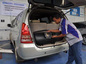 Pemasangan tabung dan konverter kit pada mobil untuk konversi dari BBM ke BBG.