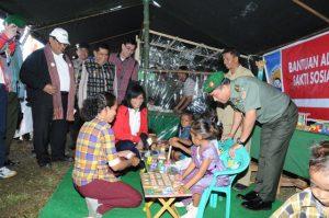 Direktur Utama Pertamina, Karen Agustiawan (berjas merah) dan Kepala Staf TNI AD Jenderal TNI Moeldoko (kanan) bercengkerama dengan para siswa PAUD dalam Bakti Sosial di Desa Loluna Puebulak, Kabupaten Belu, NTT, yang berbatasan dengan wilayah Timor Leste.